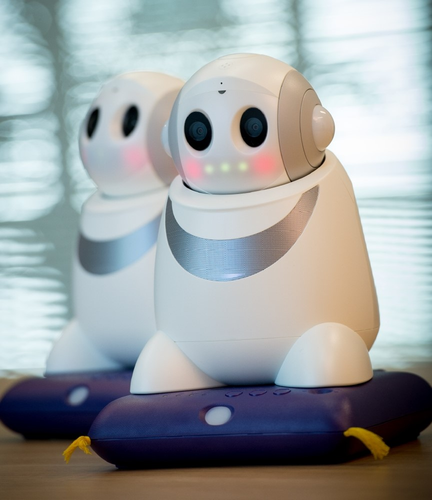 A small robots with two eyes and lights for a mouth