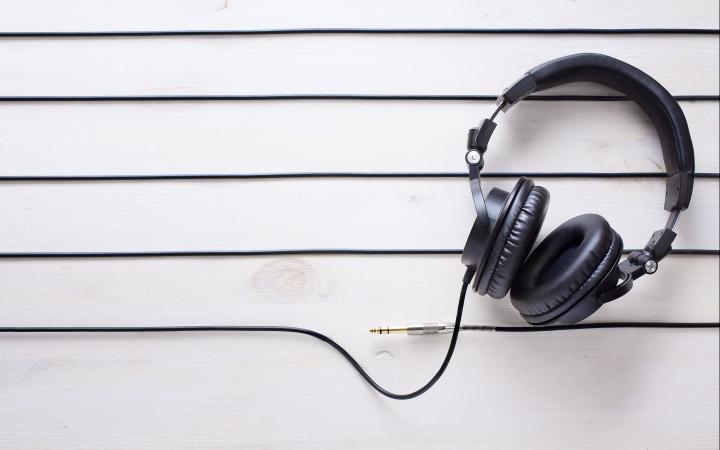Headphones lying across five horizontal lines representating a music stave