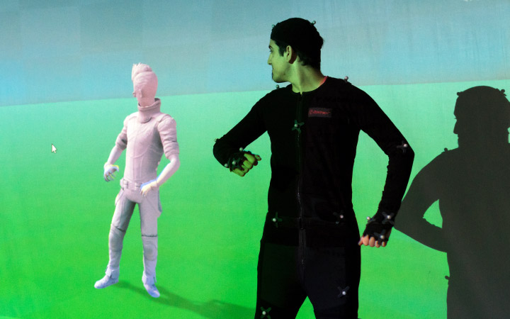 A man in front of a figure on a green screen which assumes an identical position