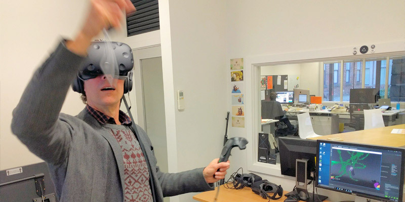 A man wears a VR headset and holds controllers in each. A monitor shows the movement path of his hands