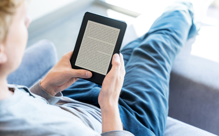 A reclining person reads on a tablet device