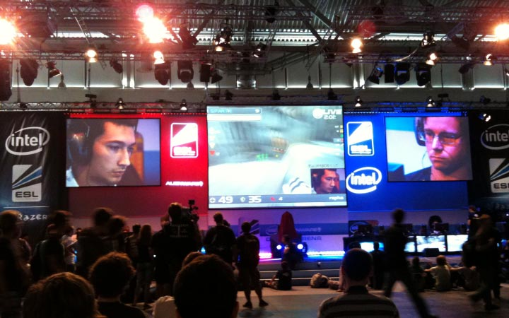 an audience watches a live multiplayer game tournament in front of giant screens