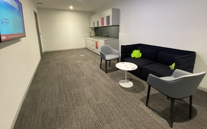 A light walled room with a couch, chairs and kitchenette