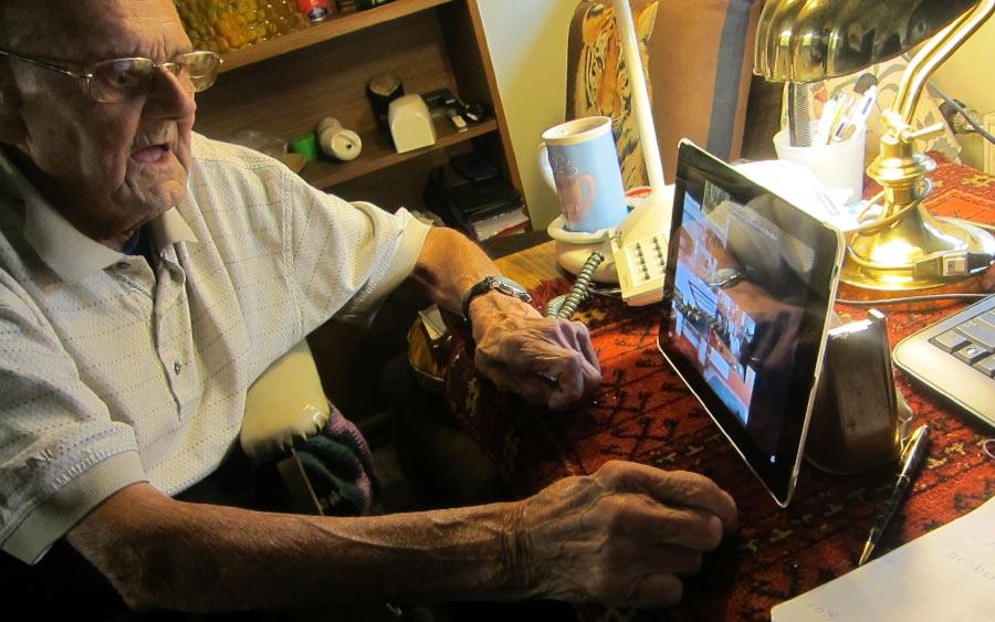 An elderly man uisng a tablet computer