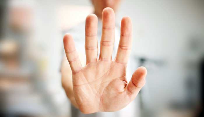 A hand, held up with the palm facing forwards, like a stop action
